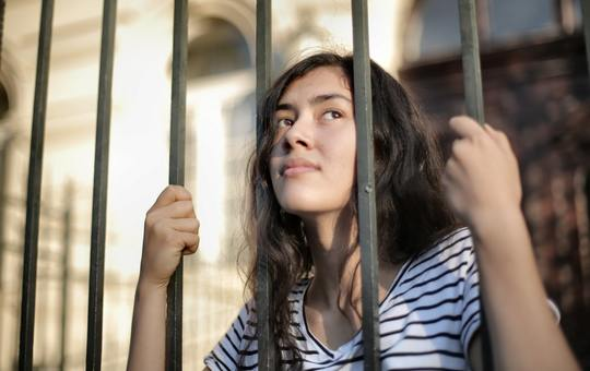 Sad isolated young woman looking away through fence with 3808803