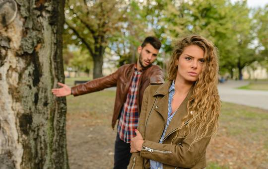 Woman and man wearing brown jackets standing near tree 984954