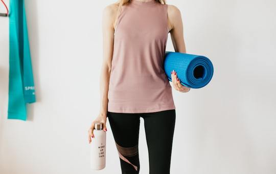 Crop sportswoman carrying sport mat and bottle of water 4498574